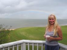 Peggy admires rainbow from our deck as storm winds diminish