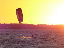 Kiter silhouetted by setting sun