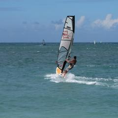 Windsurfing scene, wave on left breaking on reef